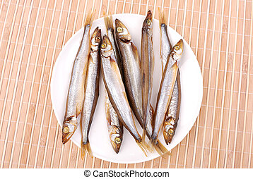 Smoked fish on a plate on a bamboo napkin