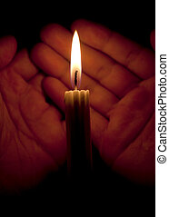 hands and a candle in the dark