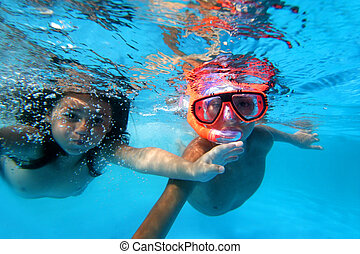 Kids swimming underwater in pool