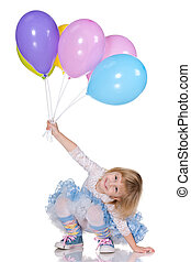 Cheerful little girl with balloons