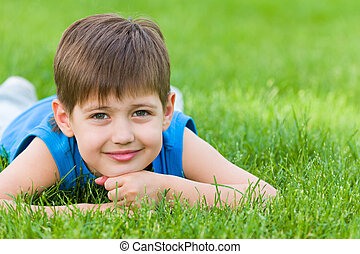 Dreams on the summer grass - A thoughtful boy is lying on...