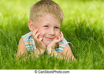 Boy imagines on the green grass - A thoughtful boy in...