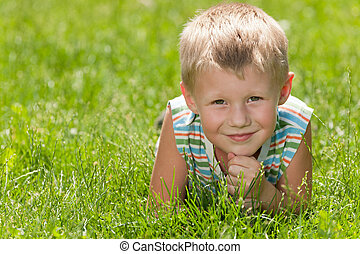 Resting on the green grass - A thoughtful boy in striped...