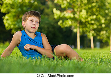 Boy imagines on the lawn - A thoughtful boy is sitting on...