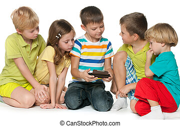 Group children plaing with a new gadget