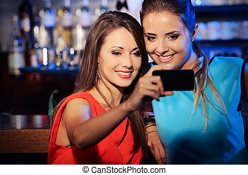 Friendship - Two happy women at nightclub party taking a...