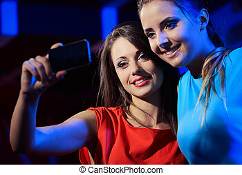 Two women enjoying with a smartphone - Two happy women at...