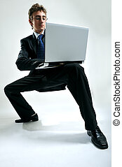 Business mobility - Young businessman using laptop in...