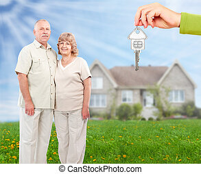 Senior couple near new home.