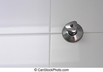 stop tap set on a white tiled wall