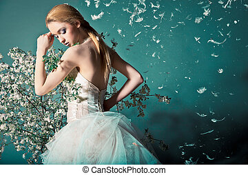 Bride in wedding dress behind bush with flowers - Portrait...