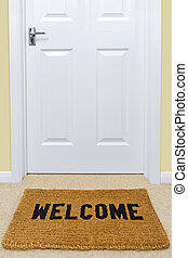 Welcome doormat outside a door.