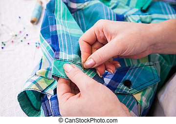 Tailor's working with a garment doing alterations