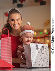 Portrait of happy mother and baby checking christmas shopping bags