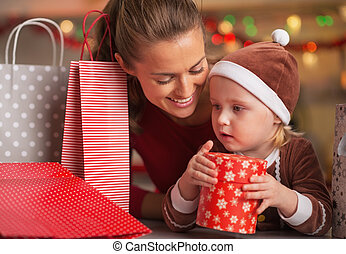 Happy mother and baby among christmas shopping bags