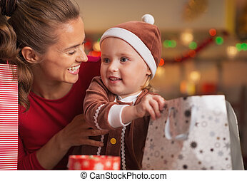 Happy mother and baby checking christmas shopping bags