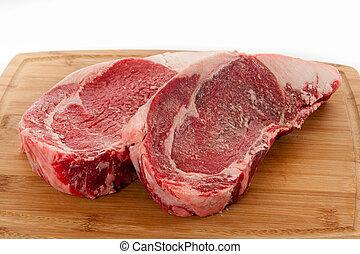 Ribeye Steaks - Beef rib eye Steaks on wooden cutting board....
