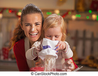 Portrait of happy mother and baby making christmas cookies