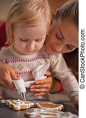Mother and baby decorating homemade christmas cookies with...