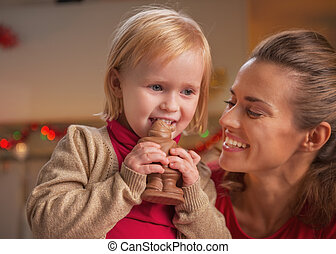 Happy mother and baby eating chocolate santa