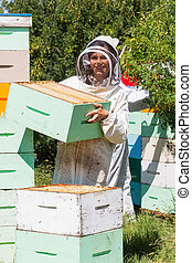 Portrait Of Beekeeper Working At Apiary - Portrait of...