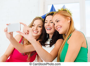 three smiling women in hats having fun with camera -...