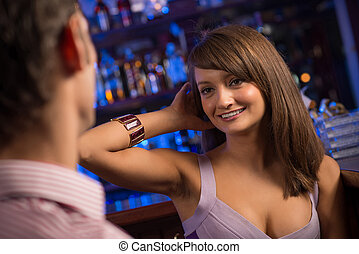 portrait of a nice woman at the bar, talking with a man at...