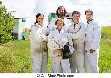 Team Of Confident Beekeepers At Apiary - Team of confident...