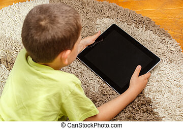 Little boy lying in the floor and looking at tablet