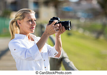 middle aged woman taking photos outdoors with DSLR camera
