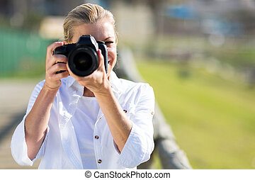 mature female photographer taking photos outdoors
