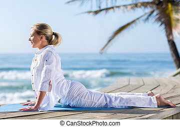 middle aged woman yoga on beach - peaceful middle aged woman...