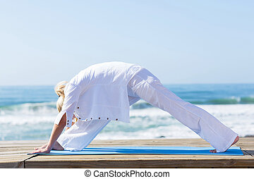 middle aged woman yoga on beach - middle aged woman doing...