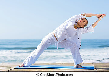 senior woman yoga on beach - active senior woman yoga...