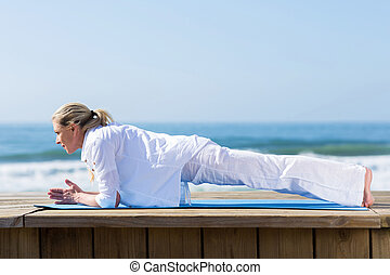 mid age woman yoga on beach - beautiful mid age woman yoga...