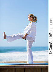 side view of senior woman stretching on beach - side view of...