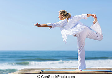 mature woman yoga pose on beach - side view of mature woman...