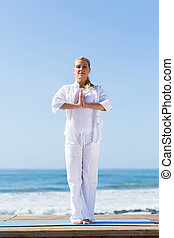 senior woman yoga on beach