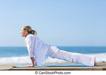 mid age woman yoga pose - fit mid age woman yoga pose on...