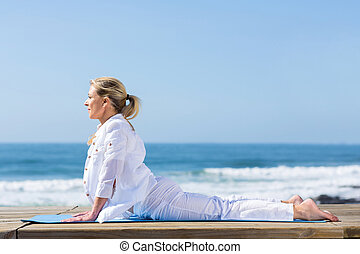 mature woman upward dog yoga position on beach