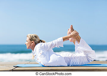 healthy mature woman doing yoga outdoors on beach