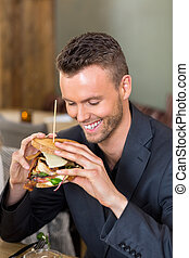 Businessman Holding Sandwich In Coffeeshop - Happy young...