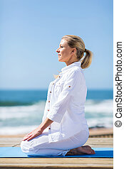 middle aged woman doing yoga on beach - beautiful middle...