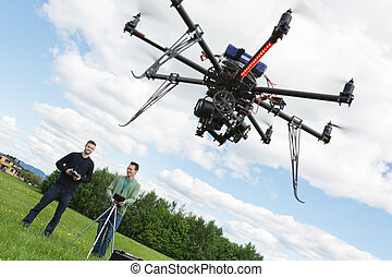 Male Engineers Operating UAV Helicopter - Young male...