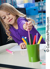 Girl Picking Sketch Pen From Case In Classroom - Cute little...