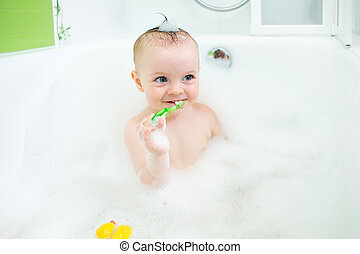 baby brushing teeth in bathroom