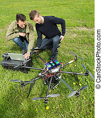 Technicians Discussing UAV - Young male technicians...