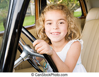 Little girl sitting in an old car and looking at camera with...
