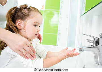 kid washing hands with adult