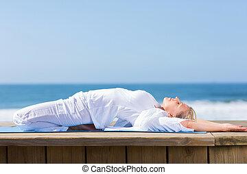 senior woman exercising yoga on beach